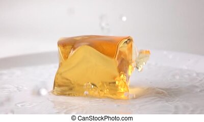 Macro super slow motion video of orange jelly falling in water