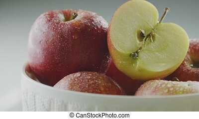 Macro tasty apples in waterdrops rotating in vase, heap of organic red appetizing fruits in dew, close up studio video. High quality 4k footage