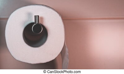 Macro view of rolling white toilet paper in a tiled bathroom with copy space available. Teal and orange style