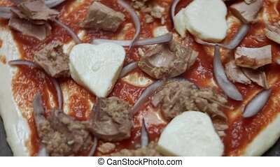 Macro view of heart shaped pizza dough with ingredients. Preparing heart shaped tuna pizza for Valentine's Day for a loved one. 4K video. Top view, rotation.
