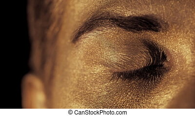 Macro view of man's face with beautiful golden body art looking to camera, eye shines brightly in the light. Focus on eye and brow. SLOW MOTION.