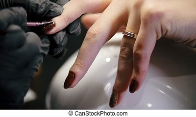 Macro view of nail polishing - female get professional...