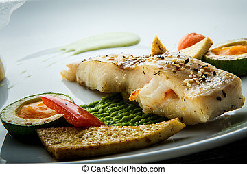 macro view on decorated baked white fish piece with garnish...