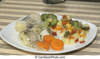 Macrourus fish with vegetables on the white plate. Adding seed oil in a food
