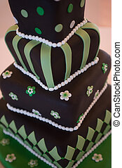 Fanciful wedding cake with tilting tiers and green and chocolate frosting