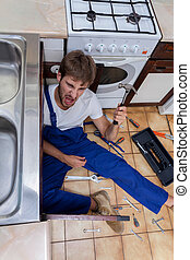 Mad man during rapair in kitchen - Mad man during rapair in...