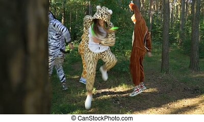 Mad people in animals costumes dances, jumps, enjoys, have fun in the forest on grass. Guys and girl dressed the costumes of zebra, jaguar, giraffe, bear, squirrel go crazy. Madness in park