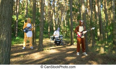 Mad people in animals costumes dances, jumps, have fun in forest on grass. Guys and girl musicians dressed the costumes of zebra, jaguar, giraffe, bear, squirrel plays music with guitar, bass, drums