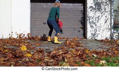 Mad playful woman with leaf blower have fun near garage. ...