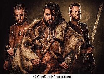 Mad vikings warriors posing in studio on dark background. -...