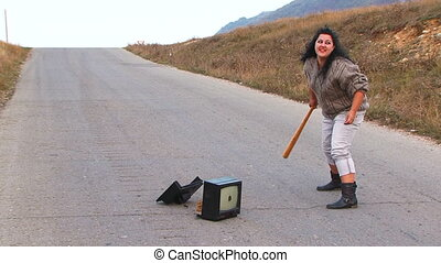 Mad Woman With Club Smashing a TV-set At Road - Slow motion...
