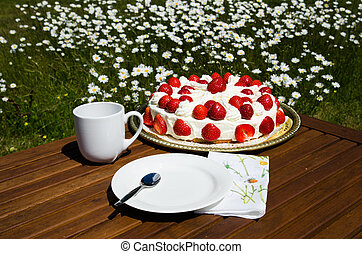 Made table with strawberry cake and coffee cup