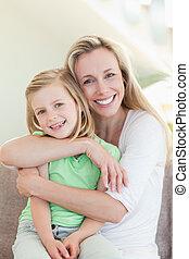 madre, abrazar, ella, hija, en, sofá