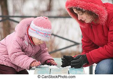 madre, con el niño, jugar con, nieve, en, banco