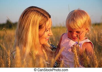 madre, con el niño, sentarse, en, campo de trigo