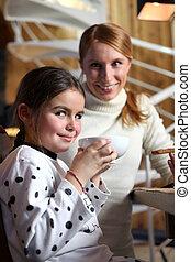 madre e hija, comer un bocado
