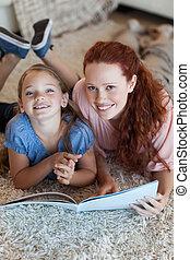 madre e hija, sobre el piso, lectura