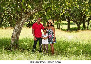 madre, padre y niño, sonriente, en cámara del juez, con, fútbol