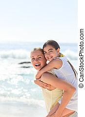 madre, teniendo, hija, un, a cuestas, en la playa