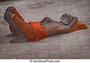 MADURAI, TAMILNADU, INDI- JAN 6: A Sadhu sleeping at Meenakshi Temple in Madurai, Tamil Nadu, India, on January 6, 2013. The two primary sectarian divisions in sadhu community are Shaiva sadhus and Vaishnava sadhus.