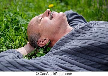 maduras, feliz, homem, mentindo, ligado, verde, grass., ele, segura, cebola, folha, em, boca, e, fecha, eyes.