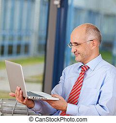 maduro, hombre de negocios, tenencia, computador portatil