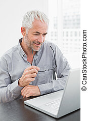 maduro, hombre de negocios, usar la computadora portátil, en, escritorio de oficina