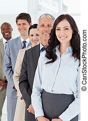 magabiztos, álló, övé, menedzser, mosolygós, dolgozók