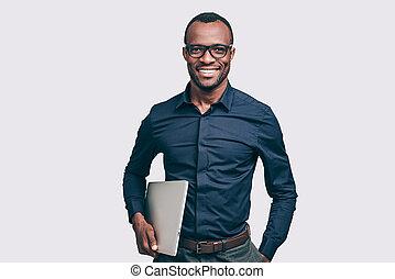 magabiztos, businessman., jelentékeny, fiatal, african bábu, szállítás, laptop, és, külső külső fényképezőgép, noha, mosoly, időz, álló, ellen, szürke, háttér