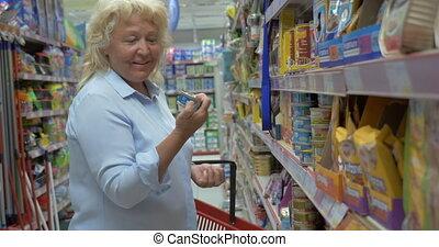 magasin, boîte, sur, femme, supermarket's, allée, aliment apprivoisé, choisir, panier, personne agee