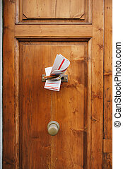 Magazines in a letterbox of a door - Multiple magazines in a...