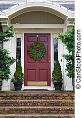 Magenta Door with Wreath on gray home with mossy red brick...
