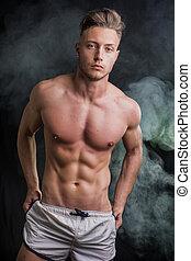 mager, athletische, shirtless, junger mann, stehende , auf, dunkler hintergrund