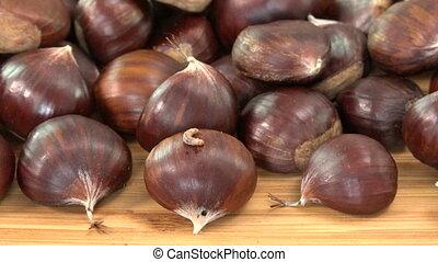 Maggot on sweet spoil chestnut, bad food on wood table -...