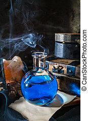 Magic concept. Blue potion in glass bottle