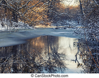 Magic evening in winter forest with frozen pond