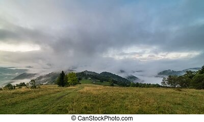 Magic foggy morning with clouds rolling over beautiful landscape at sunrise in autumn mountains. Time lapse timelapse