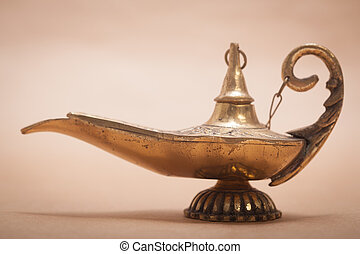 A magic genie lamp, isolated on a sand color background, in a studio shot.