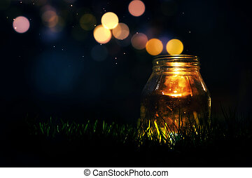 Magic Jar - Glass jar in the grass at night with magic...