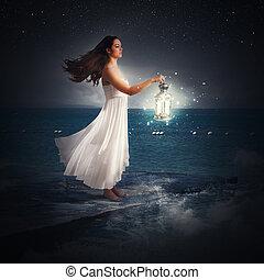 Magic night - Woman walks at night with a lantern
