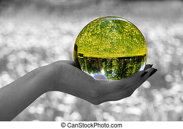 Abstraction. The glass sphere lays on a palm. The turned bright garden with dandelions is visible in sphere. All rest - is decoloured and blur.