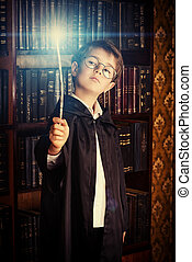 magic wand - A boy stands with magic wand in the library by...