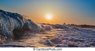 Magic wave splash close-up, at sunset. In Portugal, the Algarve area.