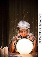 Magic woman telling future from crystal ball