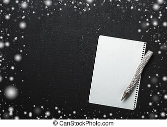 Magical Christmas theme background, snowflakes, wooden pencil and an empty letter on black table. Flat lay, top view, any holiday concept