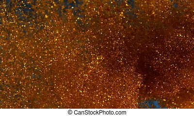 Magical ink in water. Golden shining particles with glitter...
