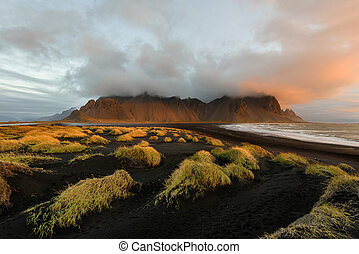 Magical landscape of Vestrahorn Mountains and Black sand dunes in Iceland at sunrise.  Panoramic view of the Stokksnes headland in a colorful seascape.