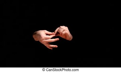 Magician doing a magic trick with coin on black background