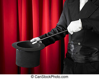Hands of the magician with magic wand and top hat.