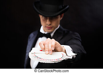 magician in hat showing trick with playing cards - magic,...